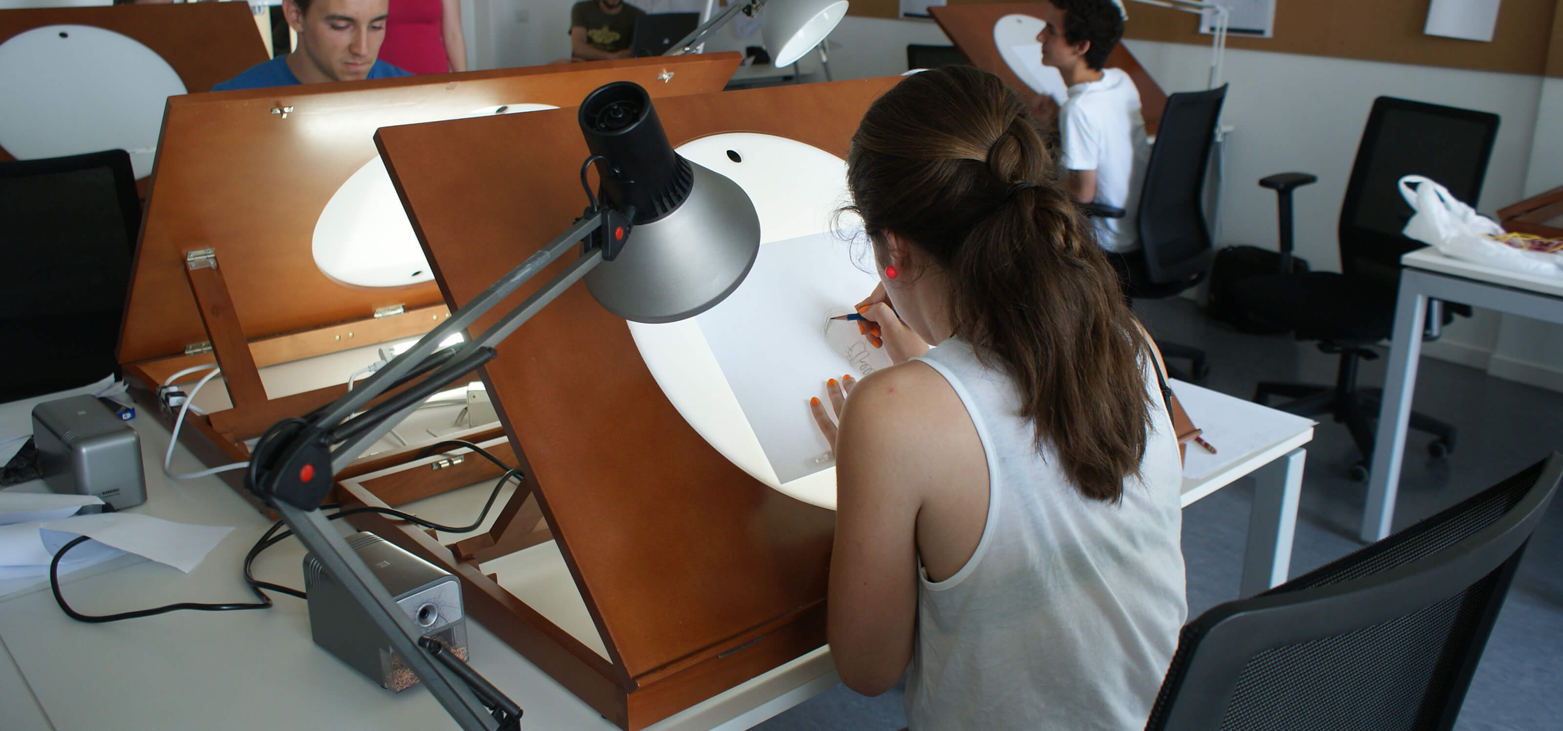 A DigiPen Europe-Bilbao student drawing on an animation light box