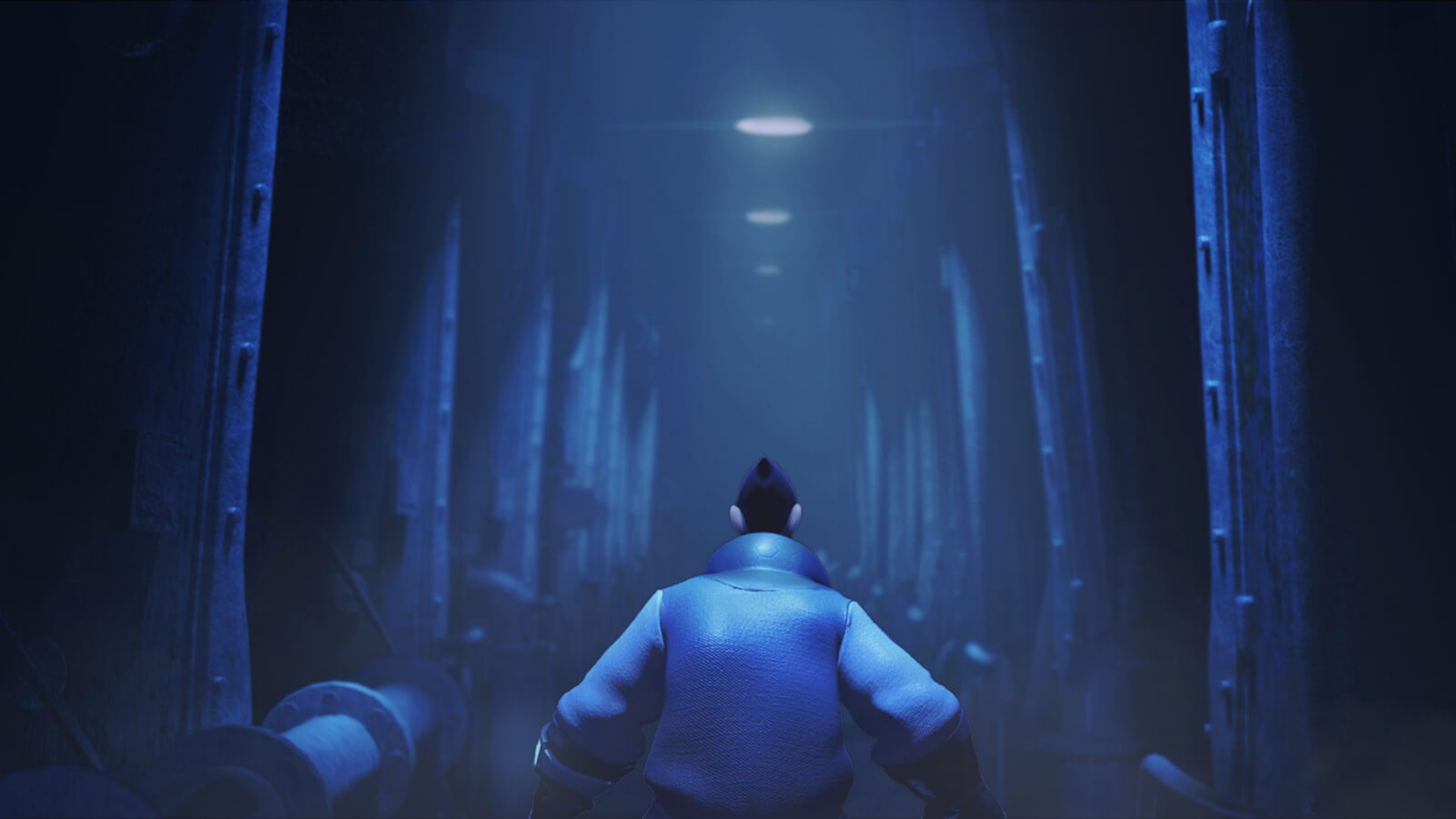 Seen from behind, a man in blue attire walks down an industrial corridor dimly lit from above