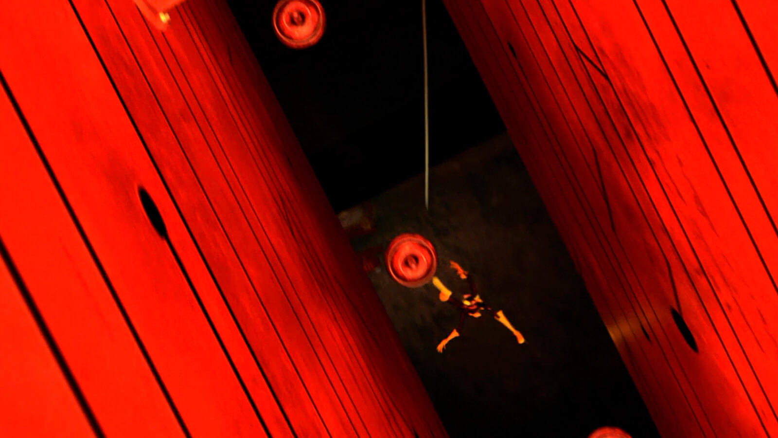A man falls through a long, narrow pit flanked by glowing red walls
