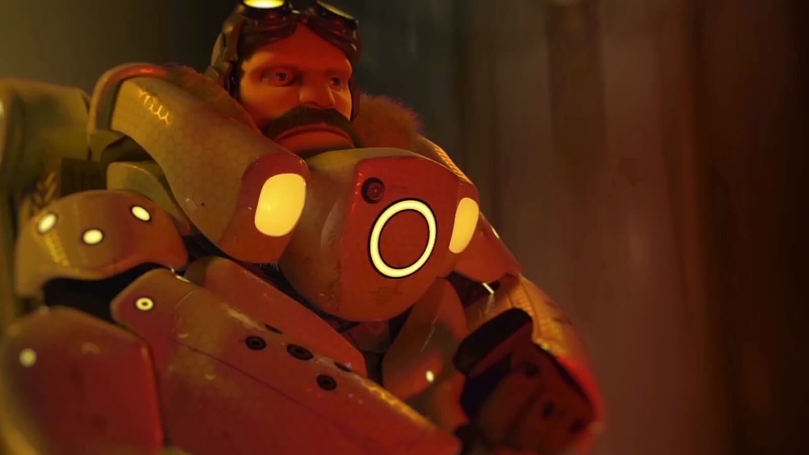 A bearded man wearing goggles and futuristic armor accented with orange lights looks ahead