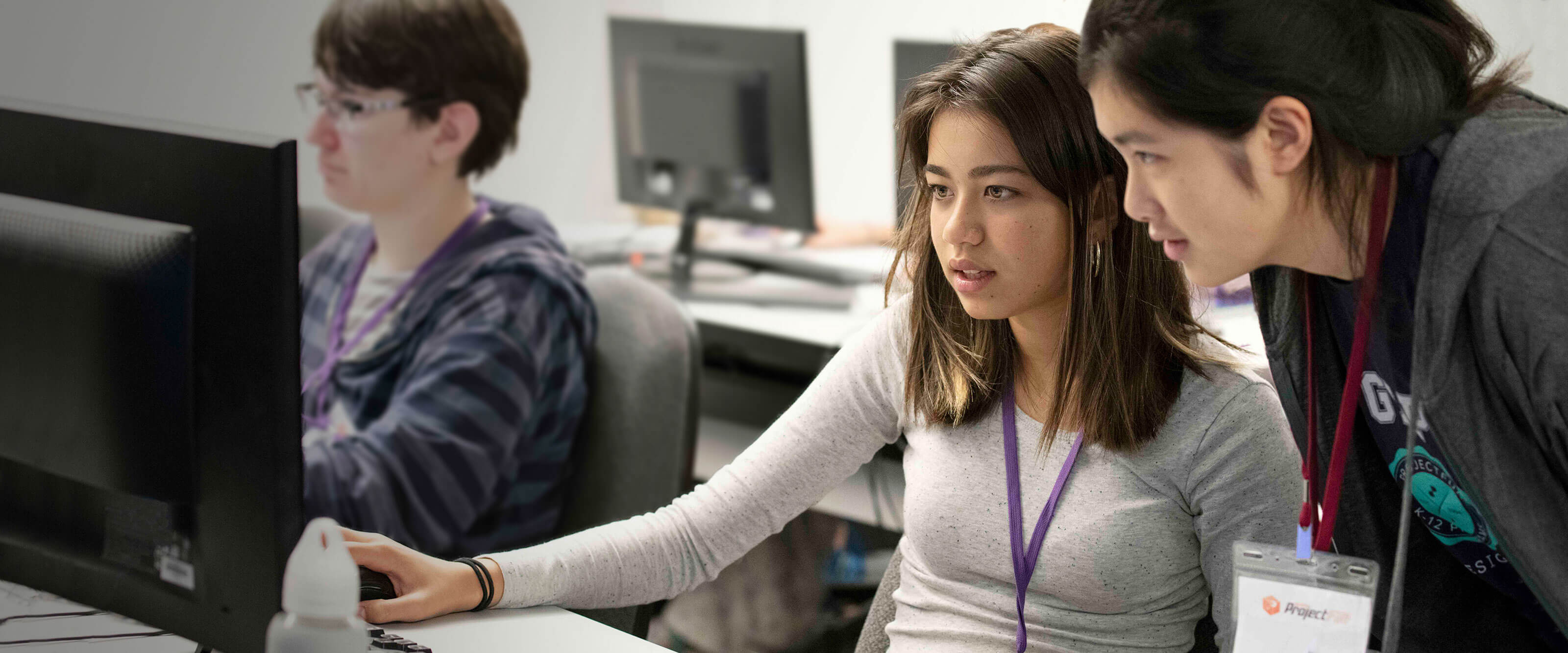 A student sits in front of a computer monitor as a ProjectFUN instructor stands over her shoulder.