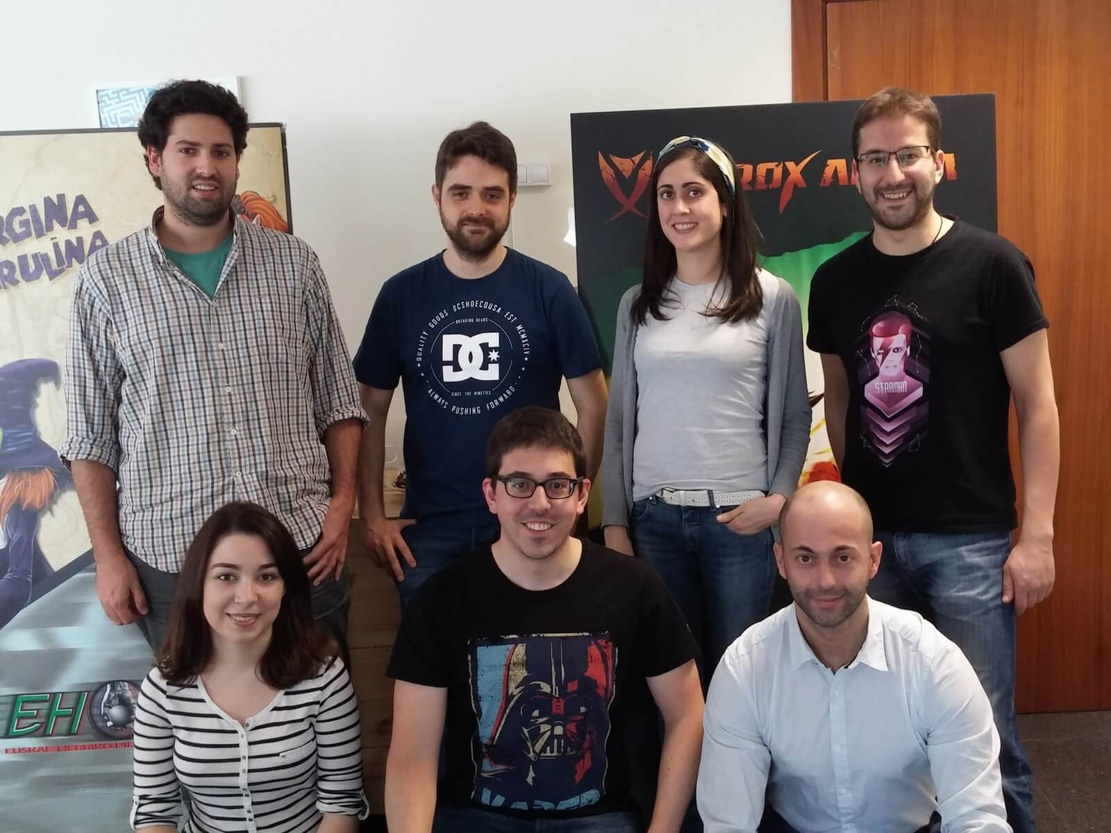 The Binary Soul team posing in front of banners depicting characters from their games