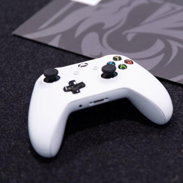 White XBox One controller next to a grey DigiPen folder